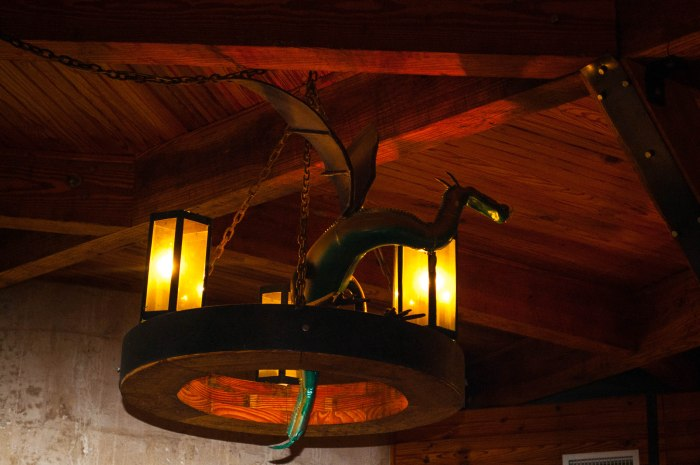 small dragon roosting on the light