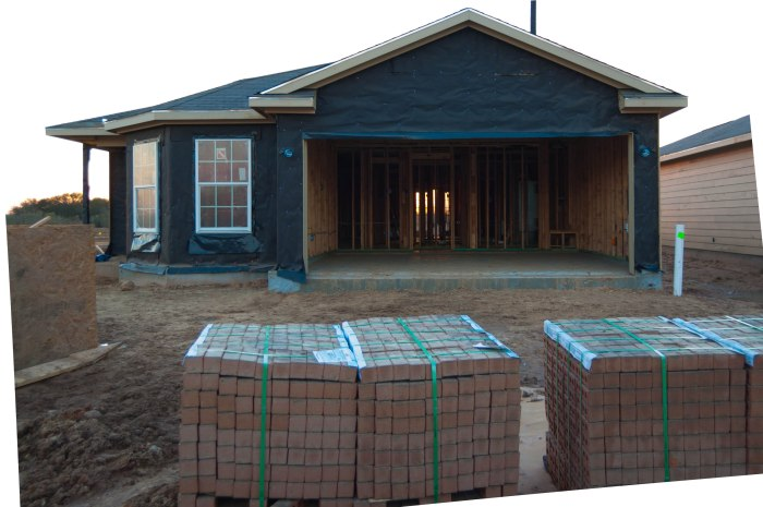 The bricks are laid out by the driveway with care in hopes that the brick mason will soon be there!